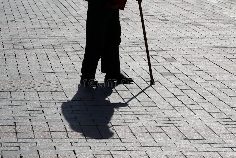 Sylwetka starej osoby odprowadzenie z trzciną, tęsk cień na bruku obraz royalty free