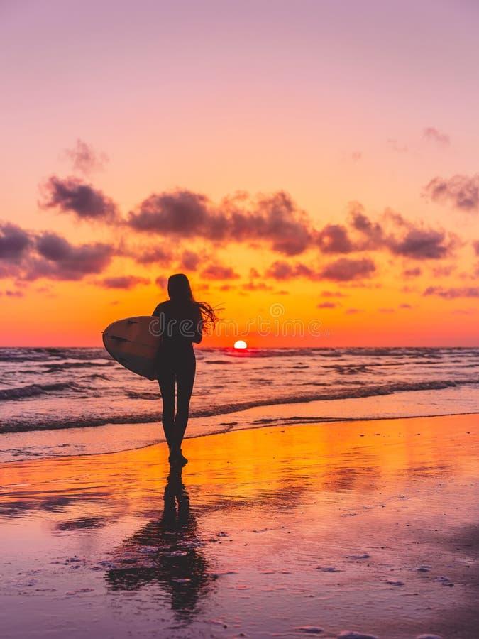 Sylwetka surfingowiec dziewczyna z surfboard na plaży przy zmierzchem Surfingowiec i ocean obrazy royalty free