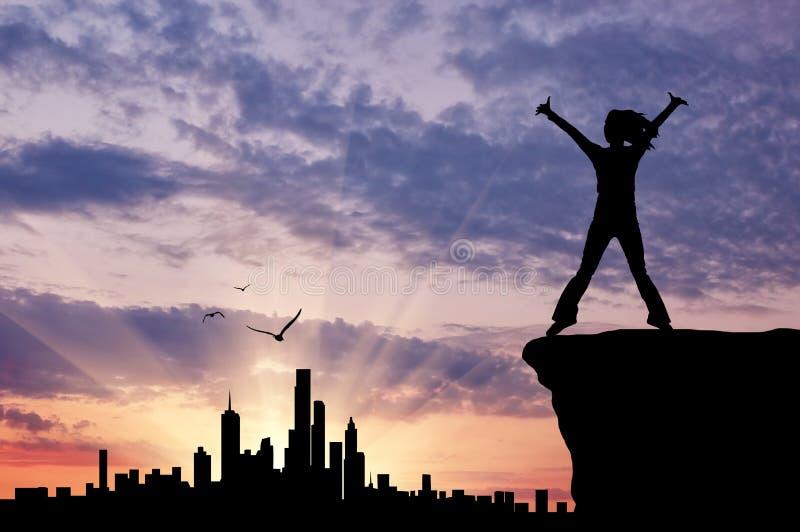 Sylwetka szczęśliwa dziewczyna patrzeje miastowego zmierzch obrazy royalty free