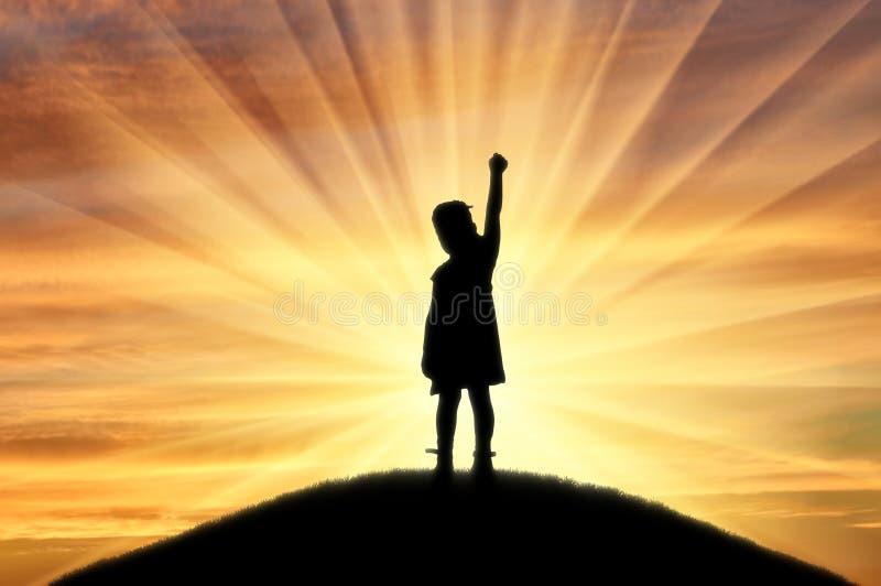Sylwetka szczęśliwa dziewczynki pozycja na górze wzgórza przy zmierzchem troszkę zdjęcia stock