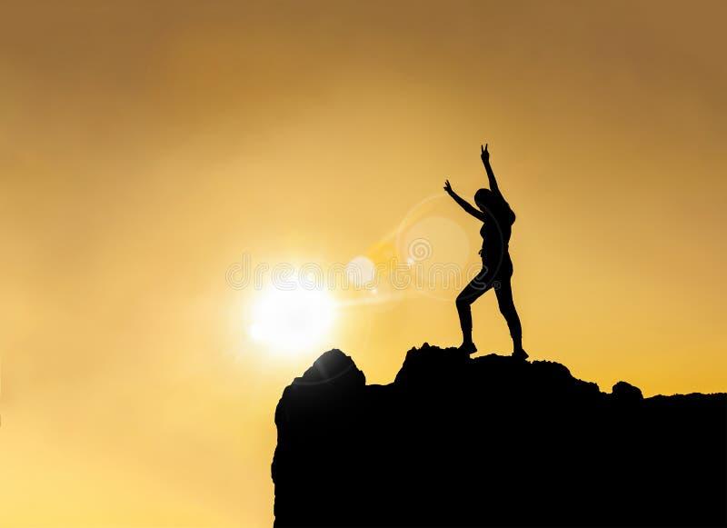 Sylwetka - szczęśliwa młoda dziewczyna na górze góry obraz stock