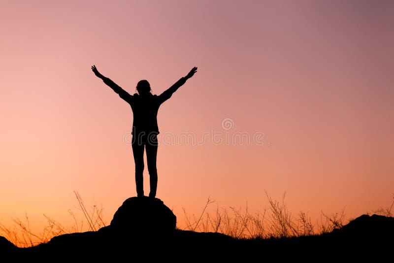 Sylwetka szczęśliwa młoda kobieta przeciw pięknemu kolorowemu niebu obraz stock
