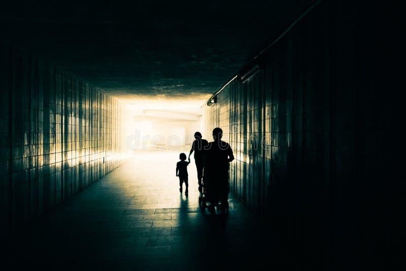 Sylwetka szczęśliwa rodzina z dziećmi podaj gospodarstwa córka matkę Ojciec i dziecko w spacerowiczu iść behind obrazy stock