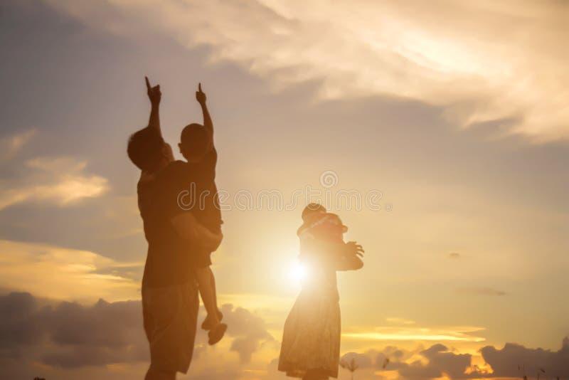 sylwetka szczęśliwa rodzinna ojciec matka, syn bawić się outdoors a i zdjęcia royalty free