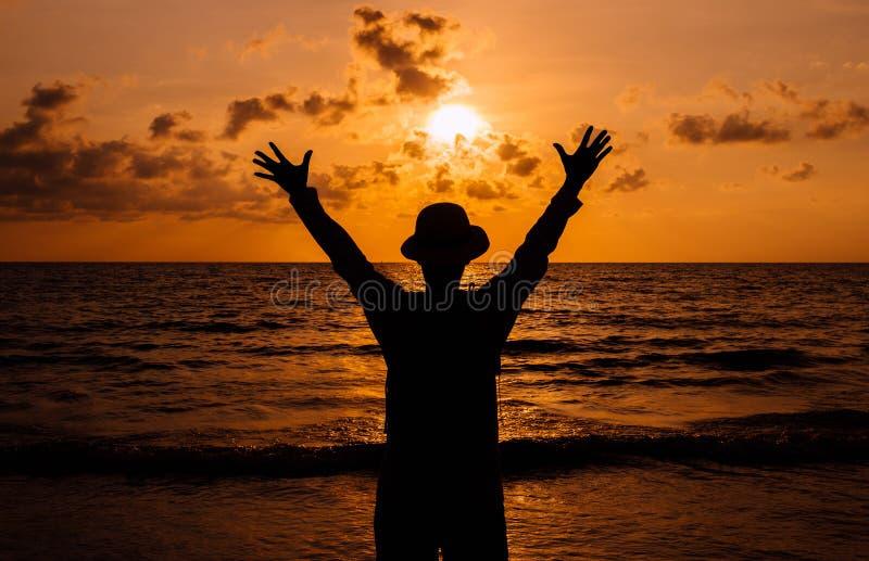 Sylwetka Szczęśliwego Człowieka podnosi ręce do zachodu słońca na morzu,Koncepcja wolności obraz royalty free