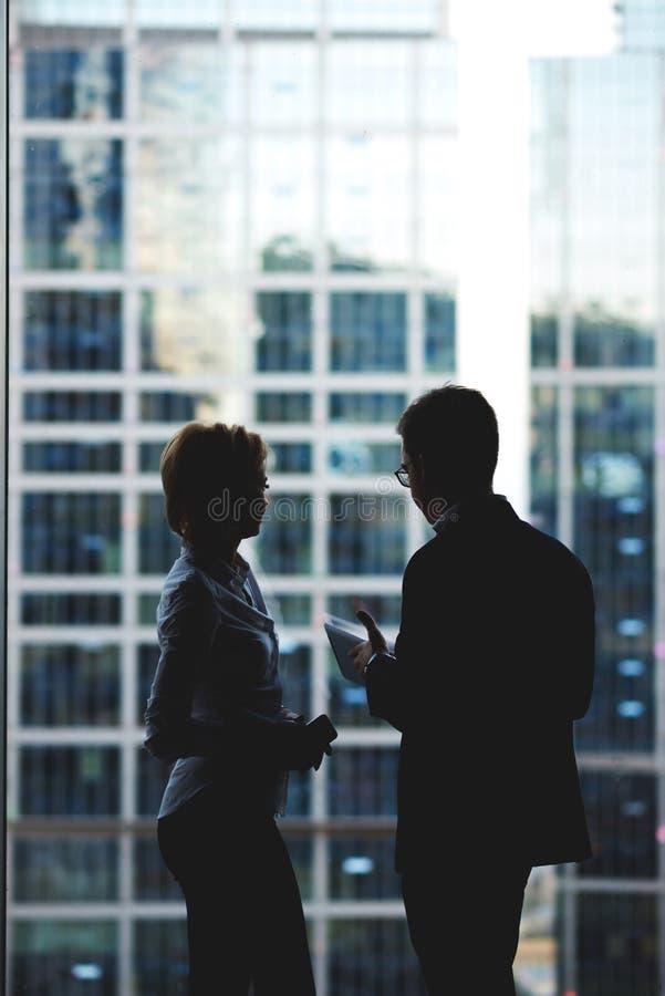 Sylwetka trzyma cyfrową pastylkę młodego człowieka dyrektor podczas gdy opowiadający jego kobieta asystent podczas pracy przerwy obrazy royalty free