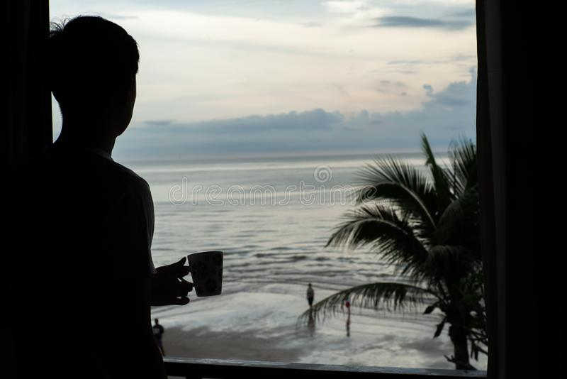 Sylwetka trzyma filiżankę i patrzeje morze mężczyzna obrazy royalty free