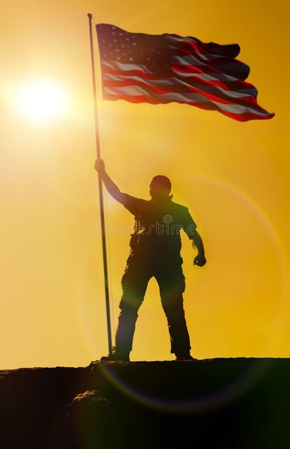 Sylwetka trzyma USA chorągwianego amerykanina na górze mężczyzna obrazy stock