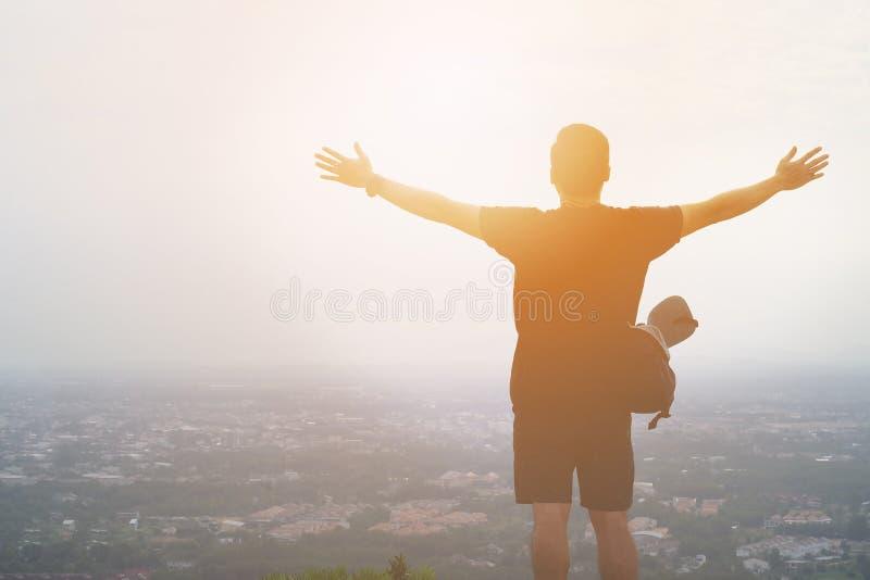 Sylwetka turystyczny mężczyzna rozprzestrzenia jego ręki szerokie jako wolność na krajobrazie lub zwycięzca zdjęcia stock