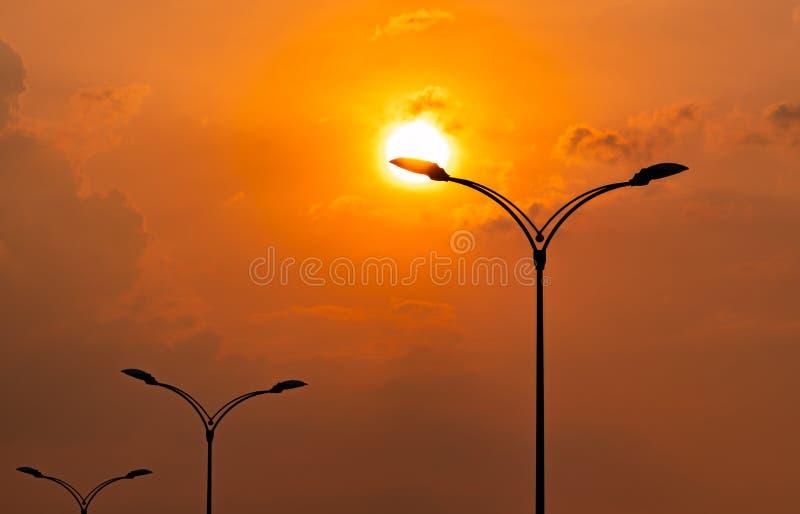 Sylwetka uliczny elektryczny słup z pięknym zmierzchu niebem, chmurami w wieczór pomarańcze i koloru żółtego i Latarni ulicznej ? zdjęcie royalty free