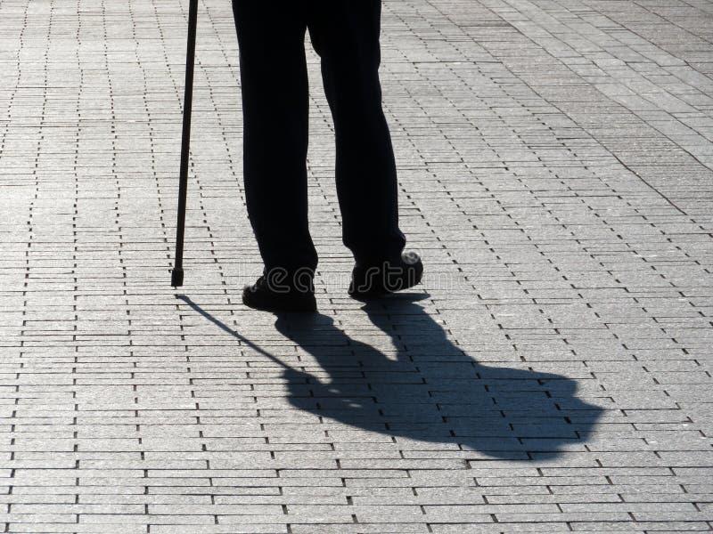 Sylwetka utyka mężczyzny odprowadzenie z trzciną, tęsk cień na bruku zdjęcia stock