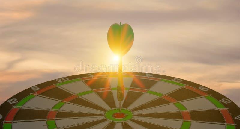 Sylwetka zielonej strzałki strzałki rzucającej się na bullseye target center dartboard na zachodzie słońca tło Koncepcja ukierunk obraz royalty free