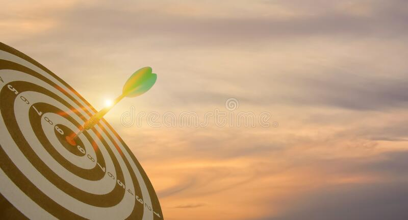 Sylwetka zielonej strzałki strzałki rzucającej się na bullseye target center dartboard na zachodzie słońca tło Koncepcja ukierunk obrazy stock