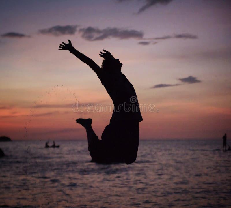 Sylwetka zrelaksowany mężczyzna doskakiwanie na plaży zdjęcie royalty free
