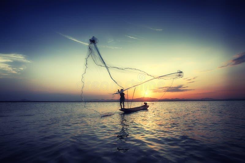 Sylwetki łódź w rzece dalej podczas zmierzchu i rybak, Tajlandia zdjęcia stock