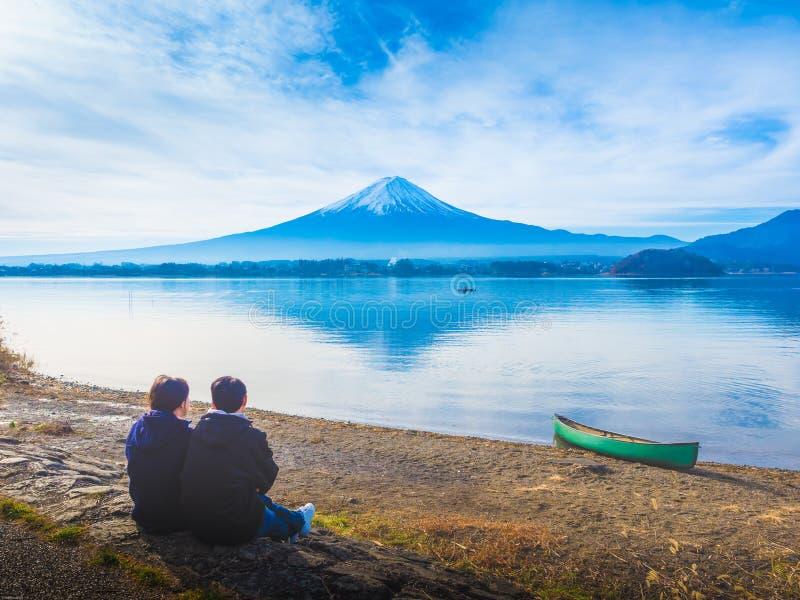 Sylwetki Asia pary podróżnik 30s 40s siedzi jezioro i widzii przy s fotografia stock