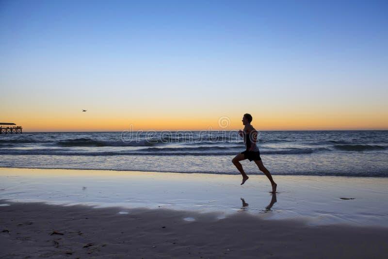Sylwetki atlety biegacza młody dynamiczny mężczyzna z dysponowanym silnym ciała szkoleniem na lato zmierzchu plaży biegać bosy w  obraz stock