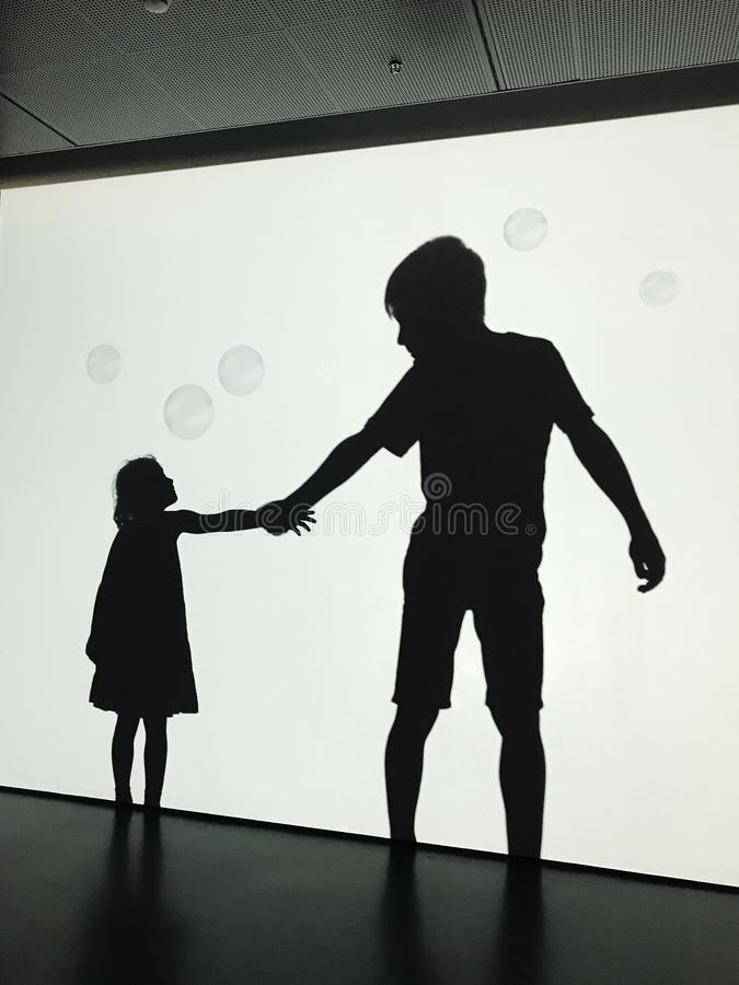 Sylwetki chłopiec i dziewczyny mienia ręki obrazy stock