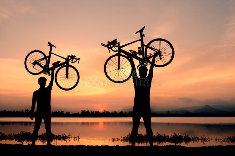 Sylwetki dwa mężczyzna stojak w akcja podnośnym bicyklu nad jego głowa zdjęcia royalty free