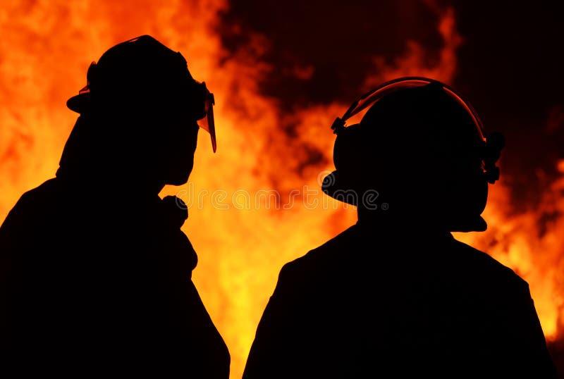 Sylwetki dwa palacze w frontowym krzaka ogieniu płoną obrazy stock