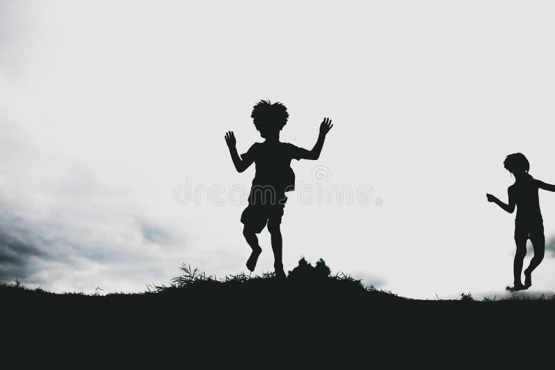 Sylwetki dzieciaki skacze od piasek falezy przy plażą obraz stock