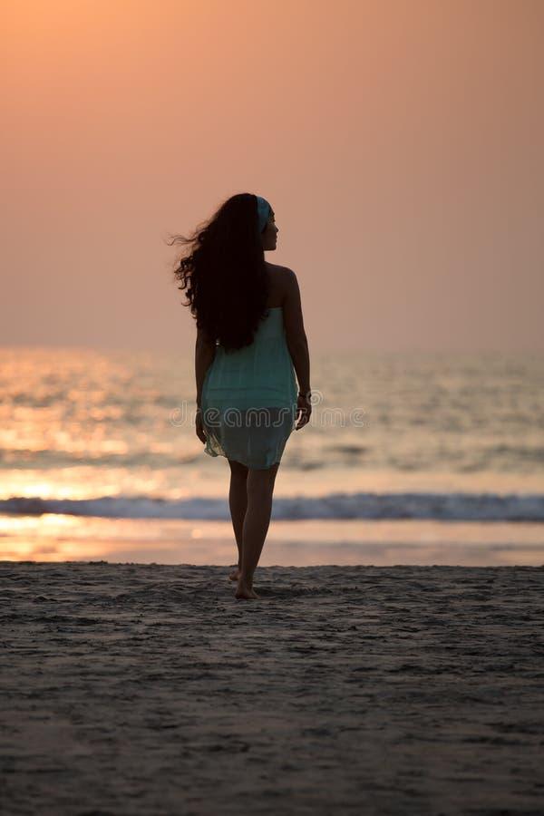 Sylwetki dziewczyny odprowadzenie wzdłuż plaży przy zmierzchem obrazy stock