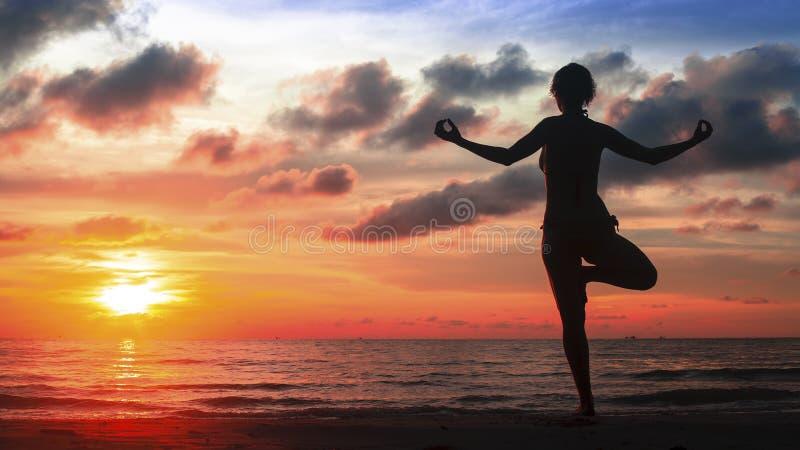 Sylwetki joga kobieta na ocean plaży przy magicznym zmierzchem zdjęcie royalty free