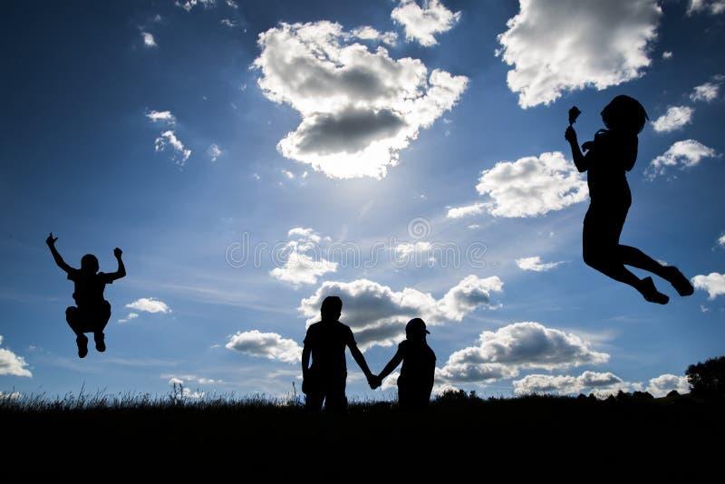 Sylwetki kobiet latać, chłopiec doskakiwanie i dwa młodzi ludzie trzyma ręki, fotografia stock