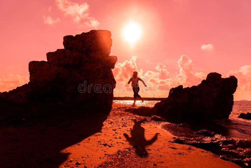 Sylwetki kobiety ćwiczenie na plażowym zmierzchu i bieg Sport i zdrowy styl życia zdjęcie royalty free