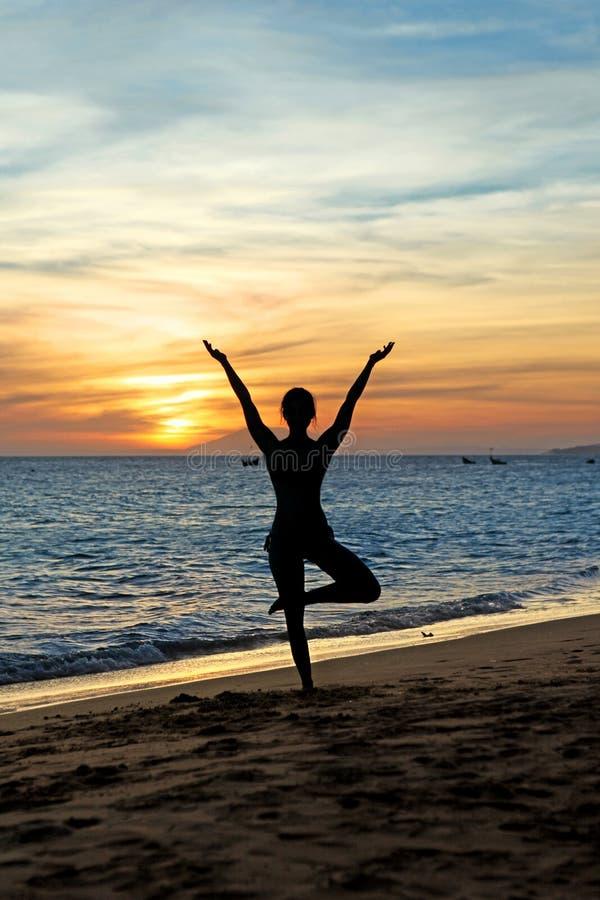 Sylwetki kobiety ćwiczy joga na zmierzchu fotografia stock