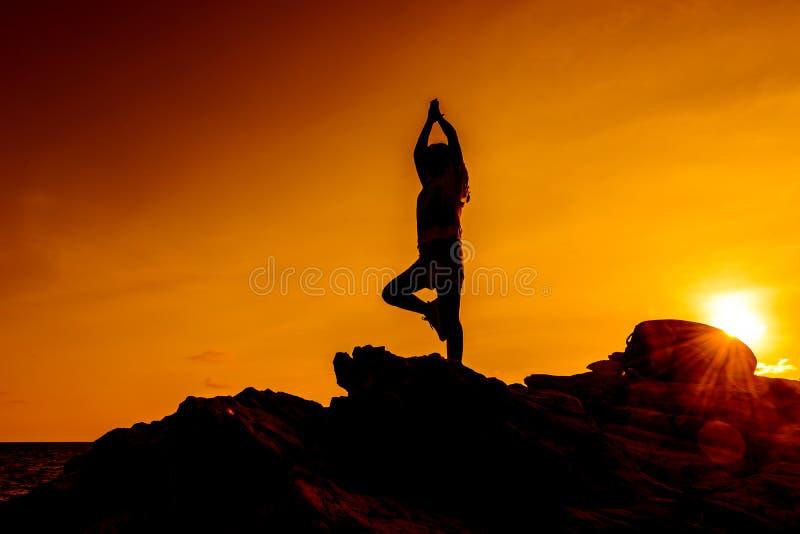 Sylwetki kobiety joga na halnym zmierzchu fotografia stock