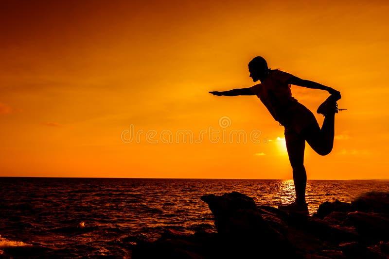 Sylwetki kobiety joga na halnym zmierzchu zdjęcia royalty free