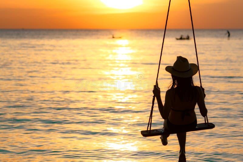 Sylwetki kobiety odzieży bikini i słomiany kapelusz huśtamy się huśtawki przy plażą na wakacje przy zmierzchem Dziewczyna w swimw obrazy stock