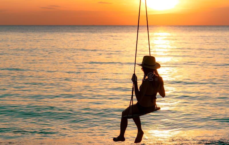 Sylwetki kobiety odzieży bikini i słomiany kapelusz huśtamy się huśtawki przy plażą na wakacje przy zmierzchem Cieszyć się i rela fotografia stock