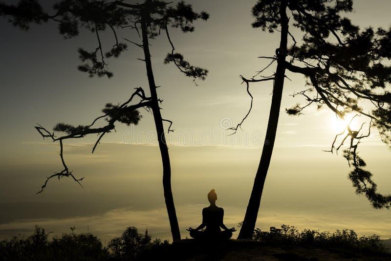 Sylwetki kobiety praktyki joga z zmierzchu tłem zdjęcie stock