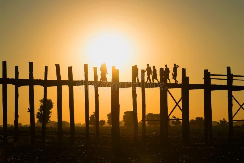 Sylwetki ludzie chodzi na U bein moscie przy zmierzchem Amarapura, Myanmar zdjęcia royalty free