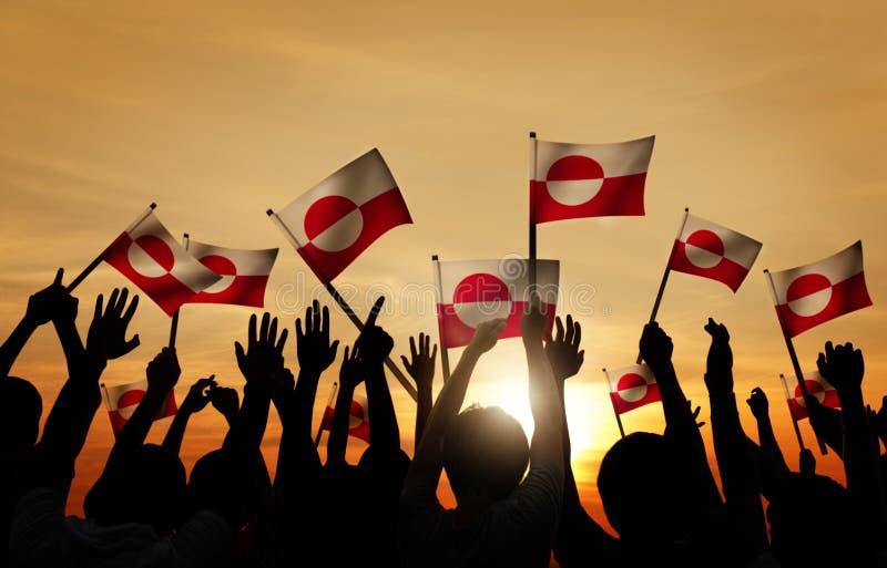 Sylwetki ludzie Trzyma flaga Greenland obraz stock
