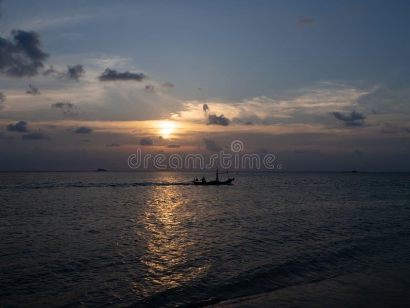 Sylwetki ludzie w kajaku w promieniach położenia słońce przeciw tłu chmury zdjęcie stock