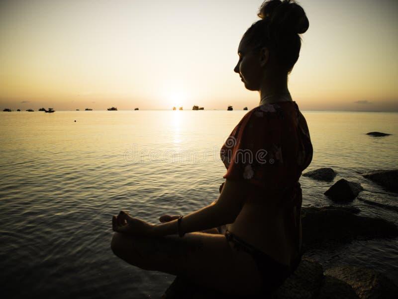 Sylwetki młodej kobiety ćwiczy joga na plaży przy zmierzchem zdjęcia stock