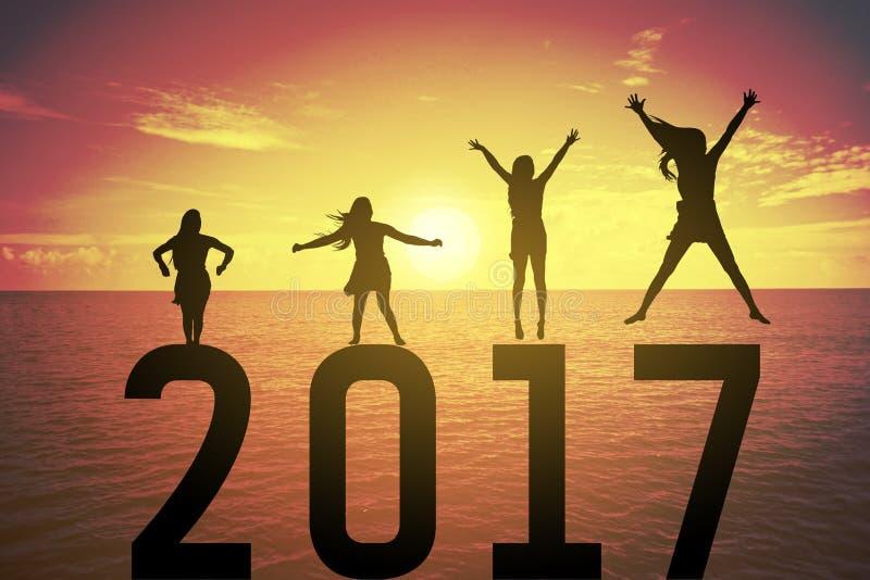 Sylwetki młoda kobieta skacze up jej rękę o szczęśliwym pojęciu na liczbach 2017 i podnosi ilustracja wektor