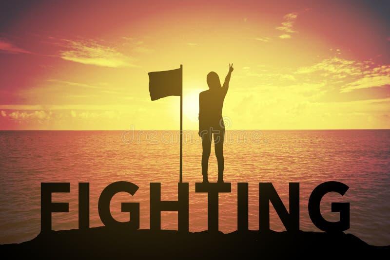 Sylwetki młoda kobieta stoi up jej rękę o zwycięzcy pojęciu na WALCZĄCYM tekscie nad i podnosi pięknym wschodem słońca lub zmierz obraz stock