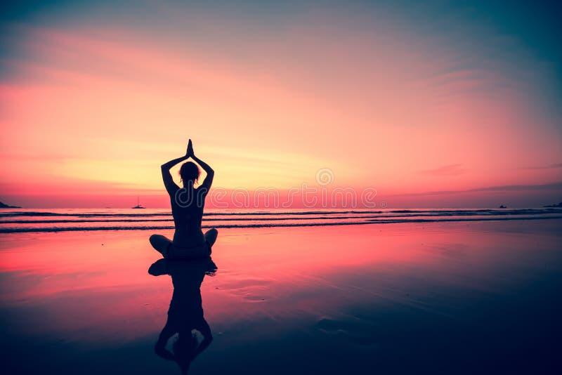Sylwetki młodej kobiety ćwiczy joga na plaży przy zmierzchem Natura obraz stock