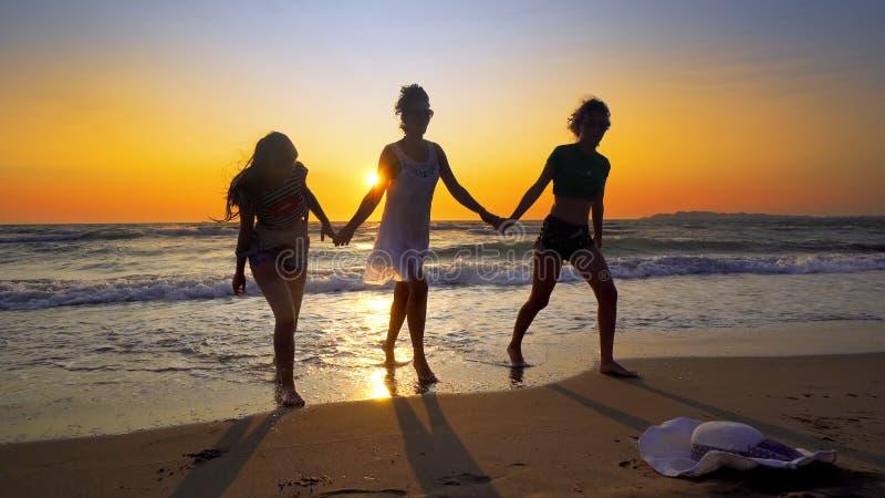 Sylwetki młody grupy ludzi doskakiwanie w oceanie przy zmierzchem zdjęcie royalty free