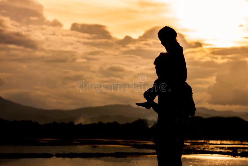Sylwetki małej dziewczynki azjatykcia jazda na father& x27; s śliwki i ramię obrazy royalty free