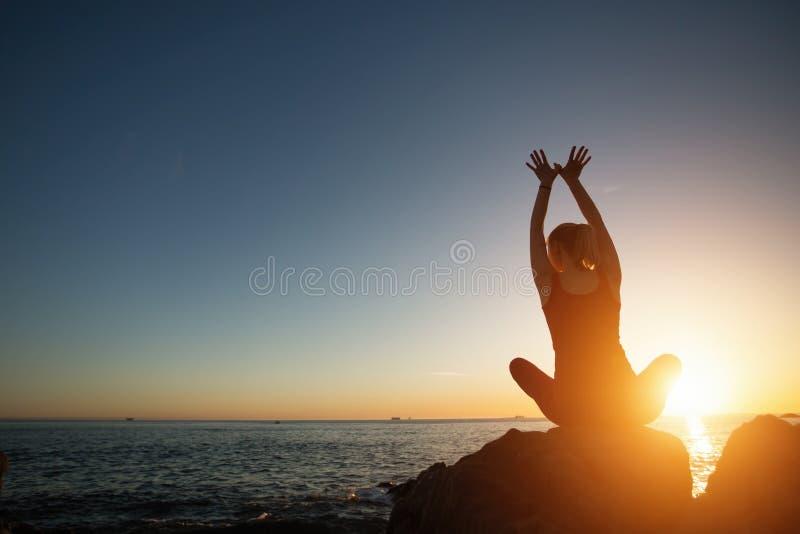 Sylwetki medytacji dziewczyna na tle denny i zadziwiający zmierzch zdjęcie stock