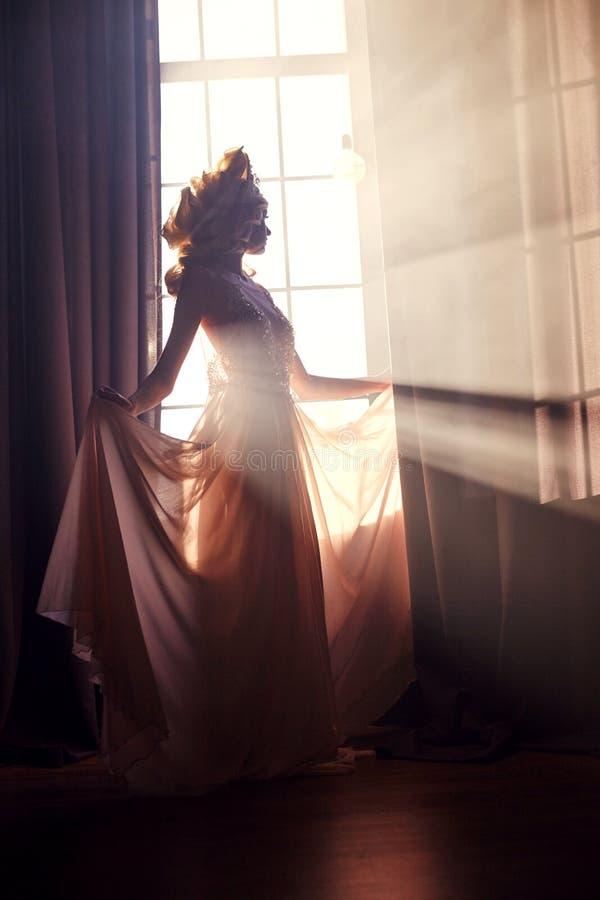 Sylwetki mody kobiety blisko okno w słońcu Cudowny p obrazy royalty free