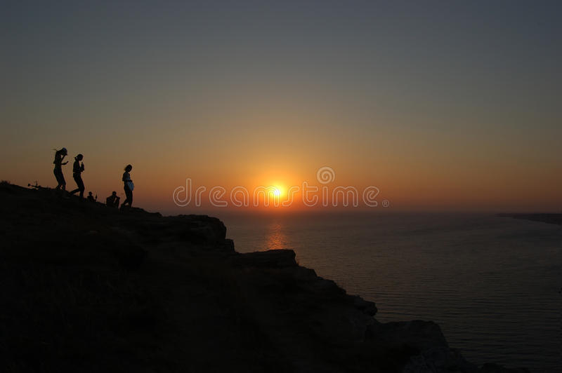 Sylwetki na zboczu góry dalej zmierzch i morze zdjęcie royalty free
