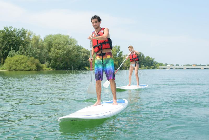 Sylwetki perfect para angażuje standup paddle abordaż fotografia royalty free
