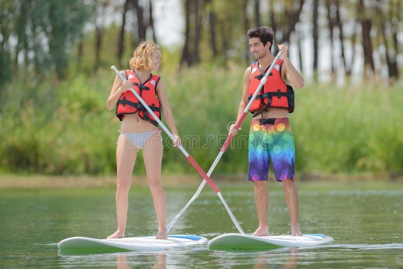 Sylwetki perfect para angażuje standup paddle abordaż obrazy stock