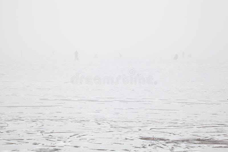 Sylwetki rybacy w mgle na zamarzniętej rzece obrazy stock